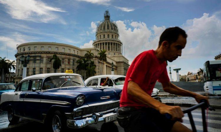 Un ciclista junto a conductores de taxis cerca del Capitolio en la Habana, Cuba (AP image)